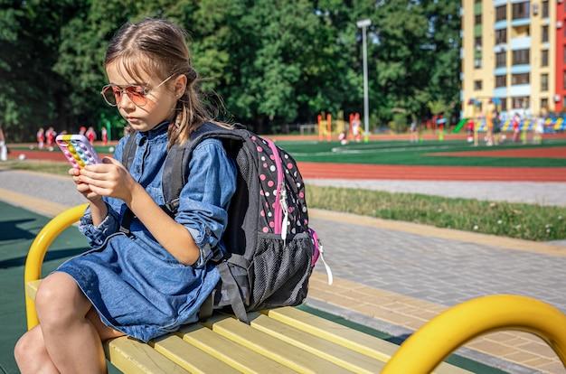 Een basisschoolleerling met een rugzak, gebruikt een smartphone, zit in de buurt van de school.