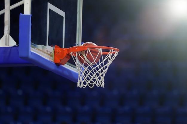 Een basketbal vliegt de ring in. op de achtergrond van een sportcomplex