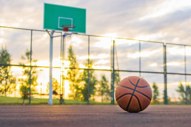 Een basketbalbal ligt op de grond op de achtergrond van een schild en een avondhemel