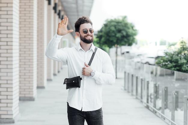 Een bebaarde, gelukkige, glimlachende, stijlvolle man groeten met vrienden in de straten van de stad in de buurt van modern kantoorcentrum