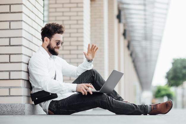 Een bebaarde, gelukkige, glimlachende, stijlvolle man zittend op de bloem in de straten van de stad in de buurt van modern kantoorcentrum en werken met zijn laptop