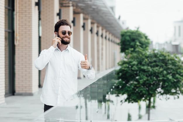 Een bebaarde, glimlachende, stijlvolle man in wit overhemd en zonnebril die in de straten van de stad staat en een mobiele telefoon gebruikt