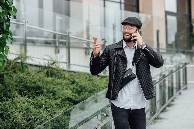 Een bebaarde, glimlachende, stijlvolle manager die telefoon spreekt in de straten van de stad in de buurt van een modern kantoor