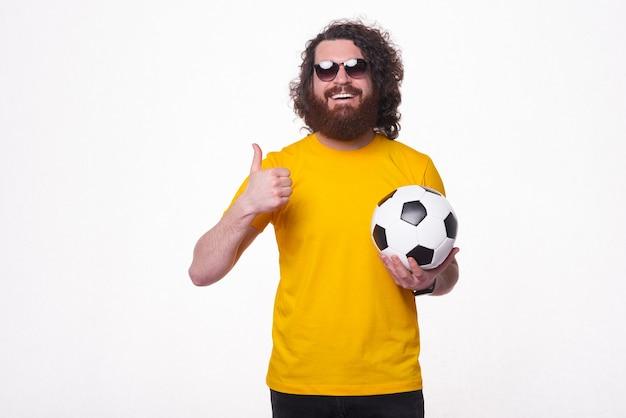 Een bebaarde jonge hipster lacht keurig naar de camera