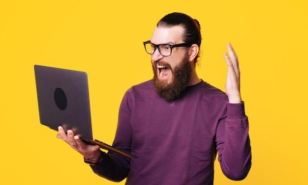 Een bebaarde jongeman met bril houdt een computer vast en schreeuwt ernaar