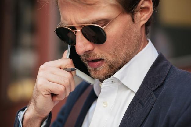 Een bebaarde knappe jongeman praat aan de telefoon terwijl hij op kantoor is