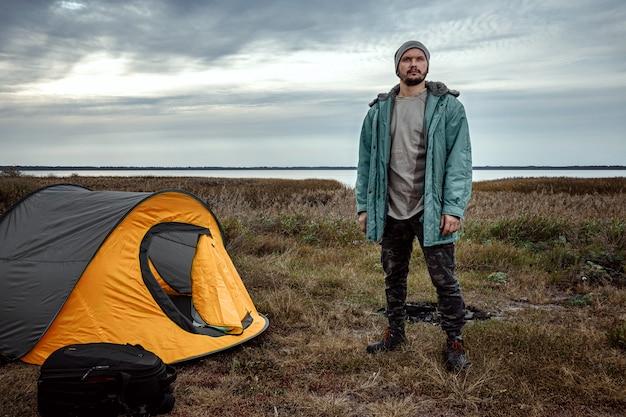 Een bebaarde man in de buurt van een camping tent in oranje natuur en het meer. reizen, toerisme, kamperen.