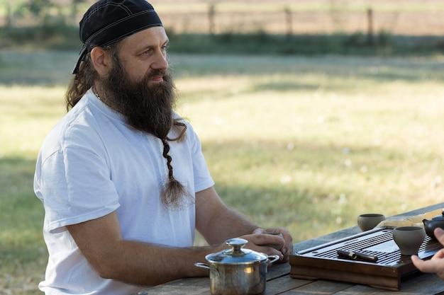 Een bebaarde man in een bandana drinkt thee op de achtergrond van de natuur.