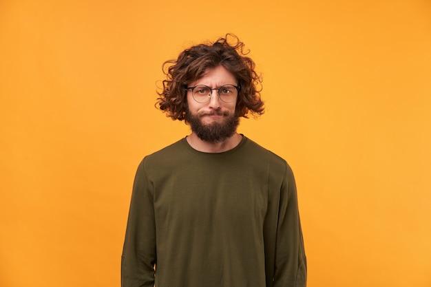Een bebaarde man in een bril met donker krullend haar kijkt naar de voorkant met een gefrustreerde uitdrukking van zijn gezicht