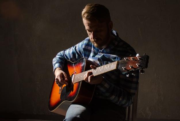 Een bebaarde man in een geruit overhemd speelt de akoestische gitaar