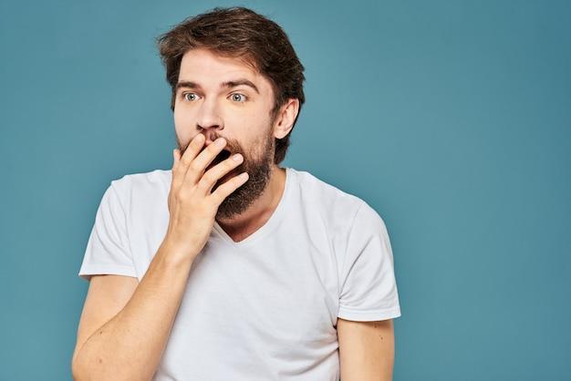 Een bebaarde man in een wit t-shirt gebaren met zijn handen emoties blauwe achtergrond