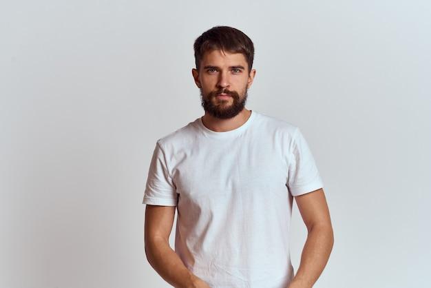 Een bebaarde man in een wit t-shirt poseren