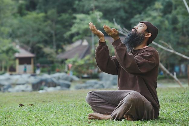 Een bebaarde man mediteert op groen gras