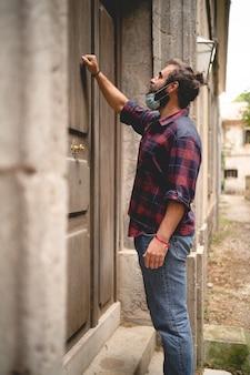 Een bebaarde man met een masker klopt op een grote deur