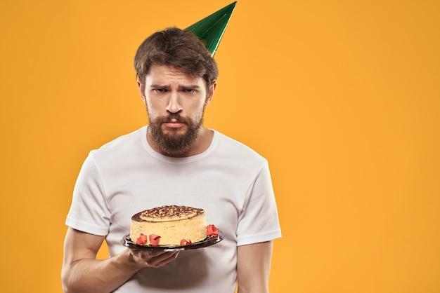 Een bebaarde man met een taart en in een pet viert zijn verjaardag terwijl hij verdrietig is