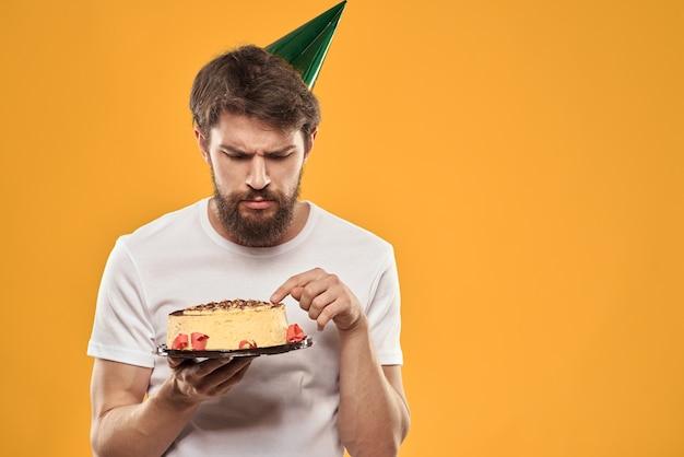 Een bebaarde man met een taart en in een pet viert zijn verjaardag