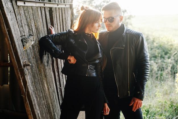 Een bebaarde man staat met zijn meisje in zwarte leren jassen in een schuur