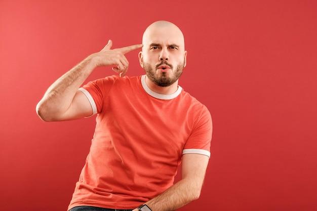 Een bebaarde man van middelbare leeftijd in een rood t-shirt op een rode achtergrond toont zijn hand een pistool tegen zijn slaap. geïsoleerd.