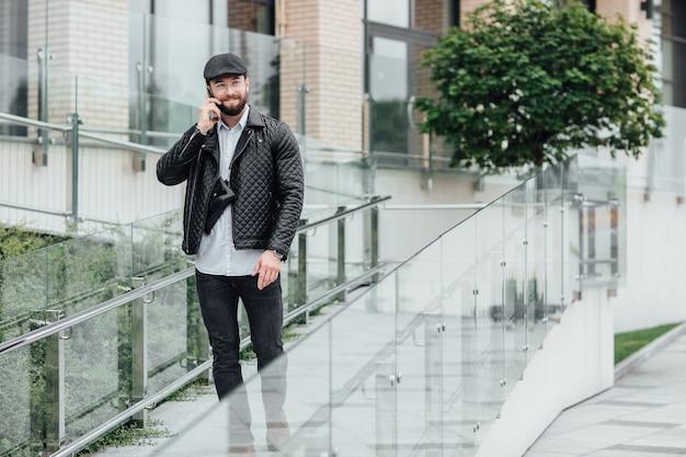 Een bebaarde, serieuze, stijlvolle manager die telefoon spreekt in de straten van de stad in de buurt van een modern kantoor