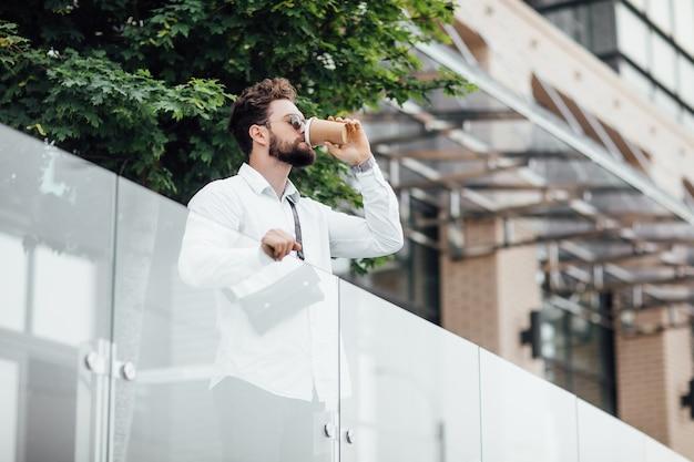 Een bebaarde, serieuze, stijlvolle manager in de straten van de stad nabij modern kantoorcentrum