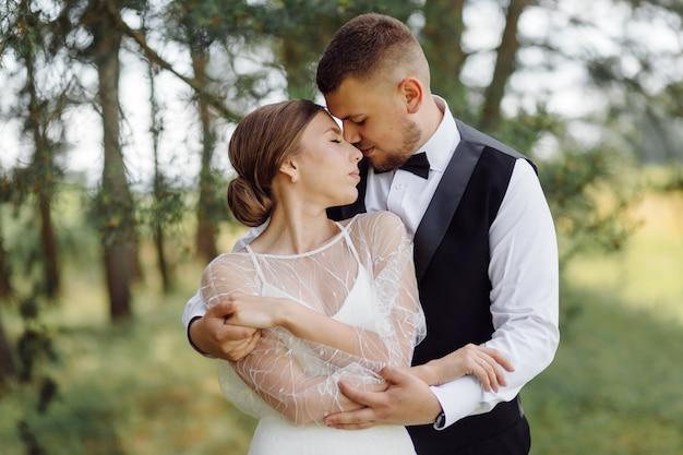 Een bebaarde, stijlvolle bruidegom in een pak en een mooie blonde bruid in een witte jurk met een boeket in haar handen staan en knuffelen in de natuur in het dennenbos.