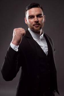 Een bebaarde zakenman in een pak met een lachend gezicht toont een gebaar van succes