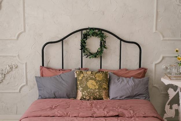 Een bed met roze stoffig beddengoed en grijze kussens in een scandinavische of klassieke stijl. op het bed hangt een krans van bladeren