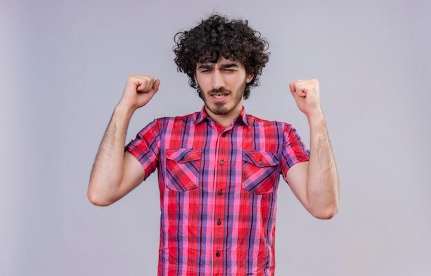 Een bedachtzame knappe man met krullend haar in een geruit overhemd die gebalde vuisten opheft