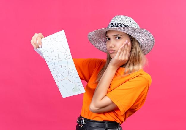 Een bedachtzame, mooie jonge vrouw in een oranje t-shirt met zonnehoed die nadenkt terwijl ze een kaart vasthoudt en naar de zijkant kijkt