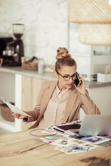 Een bedrijf leiden. drukke modeontwerper zit aan tafel met haar schetsen en praat op haar telefoon.