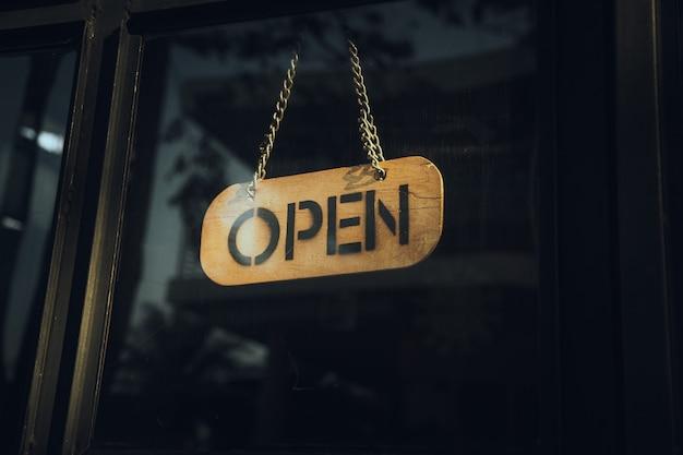 Een bedrijfsbord met de tekst 'open' op café of restaurant hangt aan de deur bij de ingang. vintage kleurtoon stijl.