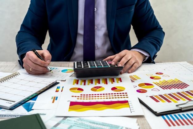 Een bedrijfsmannetje analyseert inkomsten en grafieken op kantoor. bedrijfsanalyse en strategieconcept. zakenman ontwikkelt een zakelijk project en analyseert marktinformatie, fotosessie van bovenaf