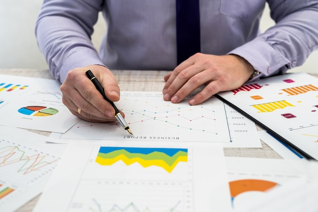 Een bedrijfsmannetje analyseert inkomsten en grafieken op kantoor. bedrijfsanalyse en strategieconcept.