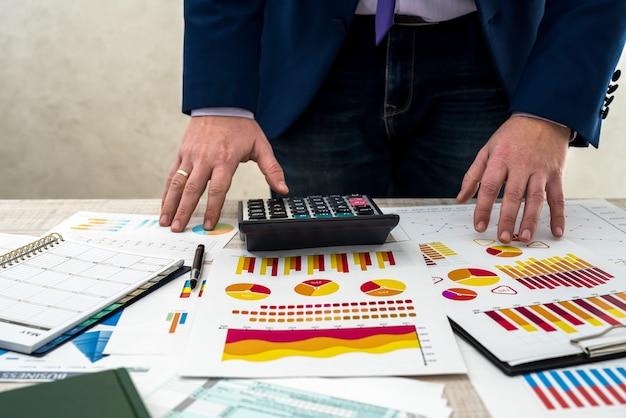 Een bedrijfsmannetje analyseert inkomsten en grafieken op kantoor