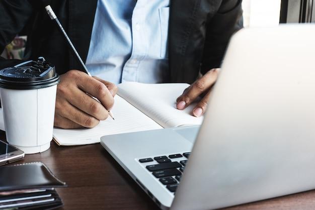 Een bedrijfsmens die laptop met behulp van bij de koffiewinkel.