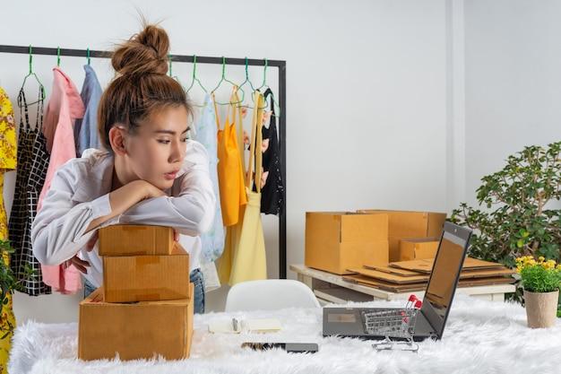 Een bedrijfsvrouw werkt online en traint om de verpakking van het klanten thuis bureau op muur te antwoorden.