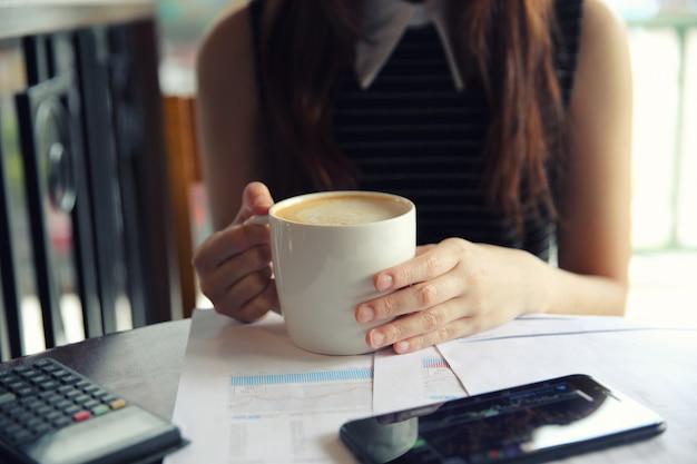 Een bedrijfsvrouwenhand met koffie en handelspapier