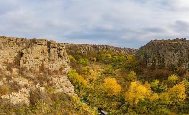 Een beek stroomt in de aktovsky canyon, oekraïne. herfstbomen en grote stenen rotsblokken rondom