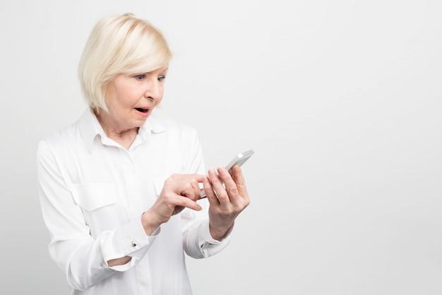 Een beeld dat van oude dame nieuwe smartphone houdt. ze weet niet hoe ze het goed moet gebruiken, omdat ze nog nooit zoiets als deze telefoon had.
