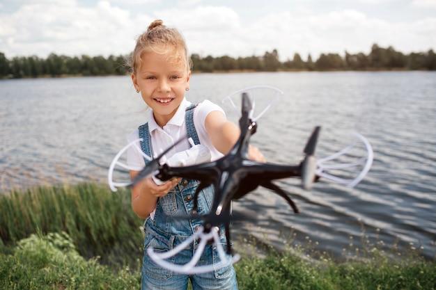 Een beeld van meisje dat zwarte drone i handen houdt. ze kijkt ernaar. het meisje bevindt zich bij de rivierkust.