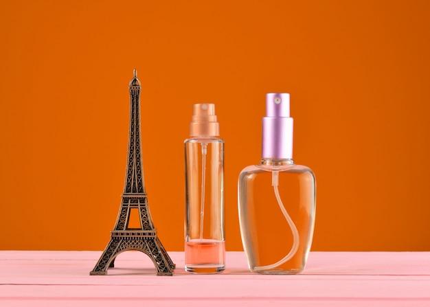 Een beeldje van de eiffeltoren, flessen parfum op oranje achtergrond