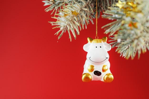 Een beeldje van een koe op een kerstkaart op een rode achtergrond, vrije ruimte voor tekst