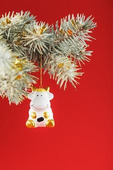 Een beeldje van een koe op een kerstkaart op een rode achtergrond