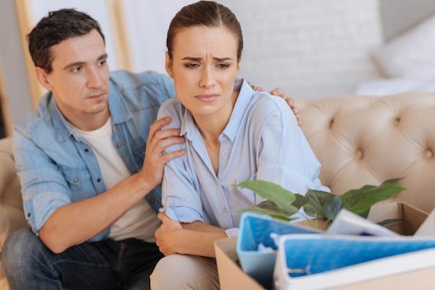 Een beetje hulp. emotioneel uitgeput ontslagen vrouw die zich afkeert van haar vriendelijke liefhebbende echtgenoot terwijl ze verdrietig is en weigert met iemand te communiceren