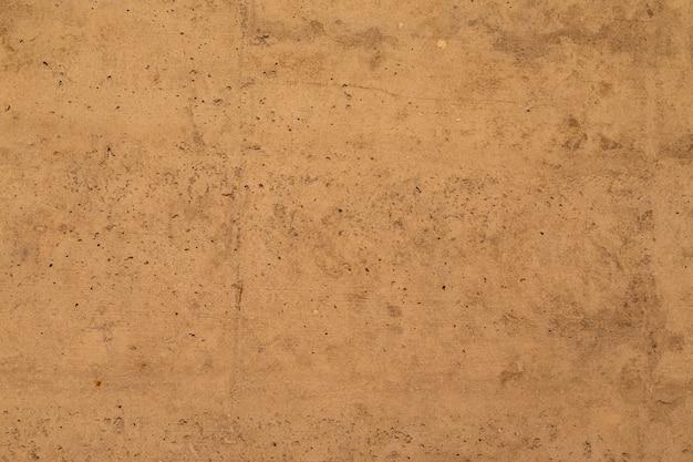 Een beige-bruine betonnen muur, interieur textuur