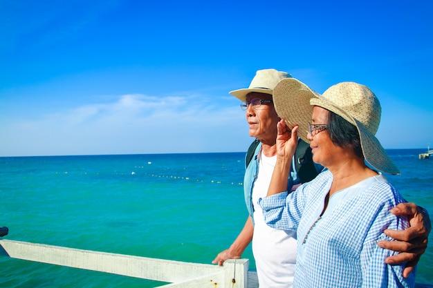 Een bejaard aziatisch paar dat elkaar koestert, gelukkig bij het overzees.