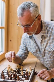 Een bejaarde die bril draagt die schaak op venstervensterbank speelt