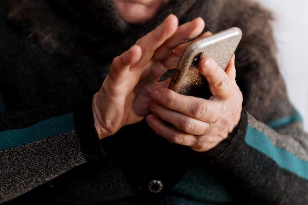 Een bejaarde grootmoeder heeft voor het eerst een mobiele telefoon