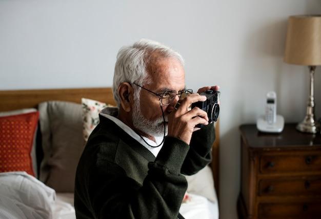 Een bejaarde indische mens bij het pensioneringshuis dat een foto neemt