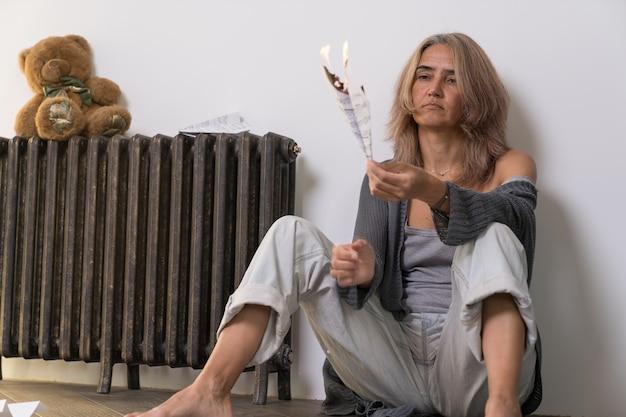 Een bejaarde vrouw met onverschilligheid op haar gezicht verbrandt een vliegtuig van een vel papier met muzieknoten